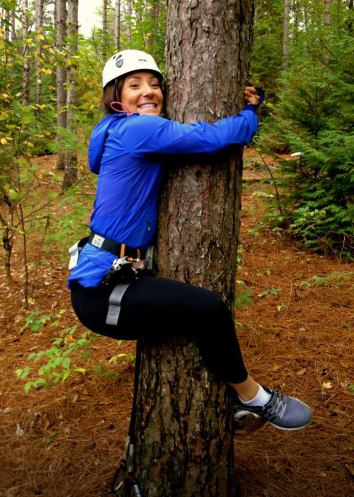 Ashley smiling and hugging a tree with her feet wrapped around in harness gear