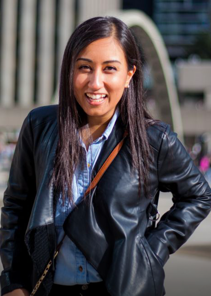 Nisha smiling with a hand in her leather jacket